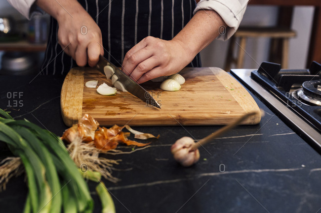 Hands of chef, chopping shallot on cutting board in kitchen