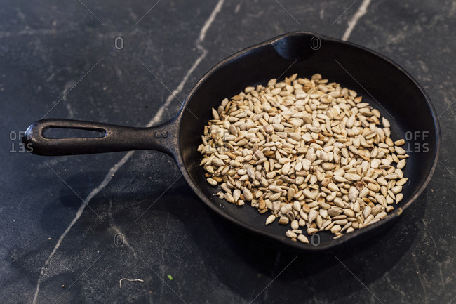 Sunflower seeds in cast iron skillet on counter