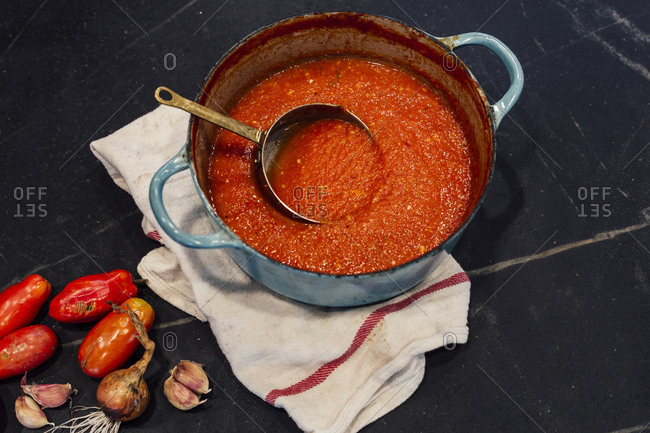 Tomato soup in turquoise pot with fresh ingredients
