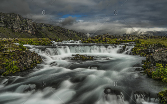 Iceland - July 31, 2015: Water Flowing Over A Rugged Landscape Under A Cloudy Sky; Iceland
