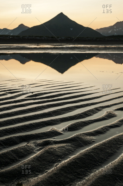 Alaska, United States of America - July 11, 2009: Silhouette Of A Peaked Mountain Reflected In Tranquil Water And Ripples In The Sand At Sunset; Alaska, United States Of America