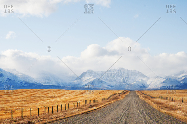 Pincher Creek, Alberta, Canada - November 18, 2009: Gravel Road Between Farm Fields And Rocky Mountains In The Distance; Pincher Creek, Alberta, Canada