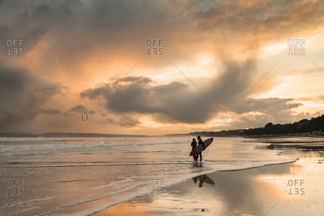 Bournemouth, Dorset, UK - March 3, 2014: A surfer couple standing on the beach under a beautiful and dramatic sunset sky. 03/03/2014.