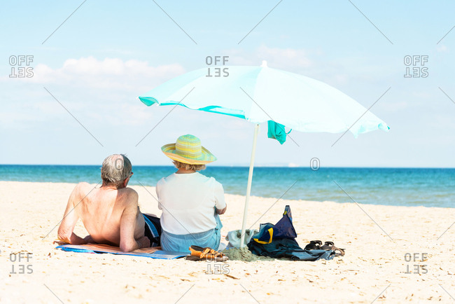 Older married couple sitting on the beach and relaxing under a blue coloured parasol