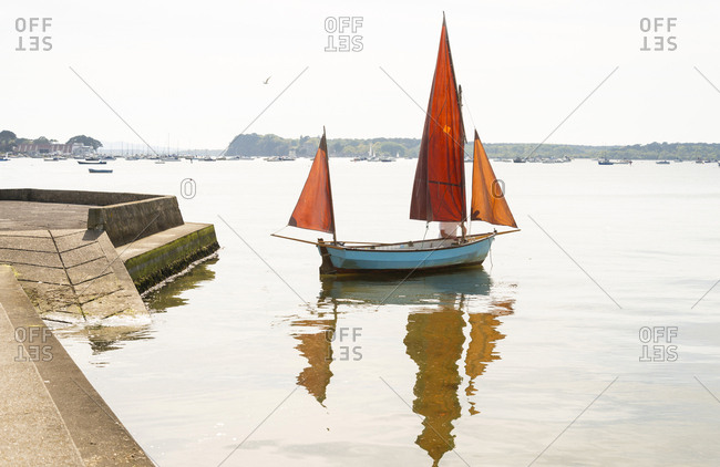 A man tends to his small sailing boat in Poole Harbour, Dorset, UK