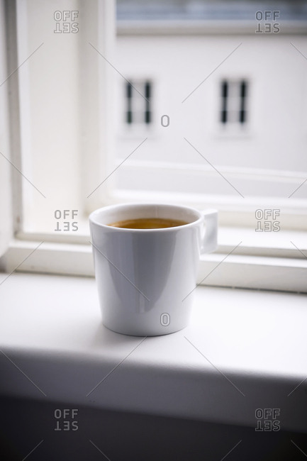 Cup of coffee on windowsill