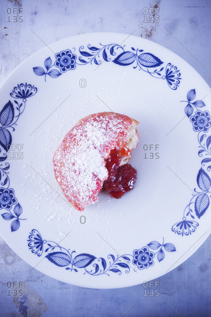 Donut filled with jelly on plate