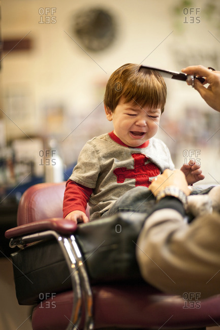 Crying baby boy getting a haircut.