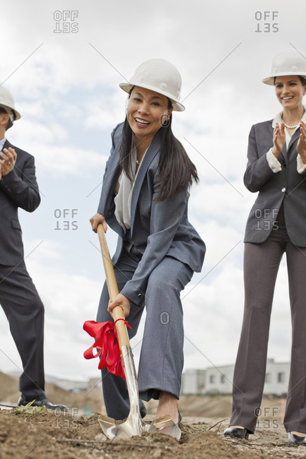 Young businesswoman wearing a suit and hardhat breaks ground for a new building development while her colleagues applaud.