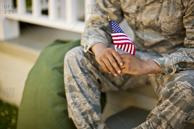American flag held by a soldier.