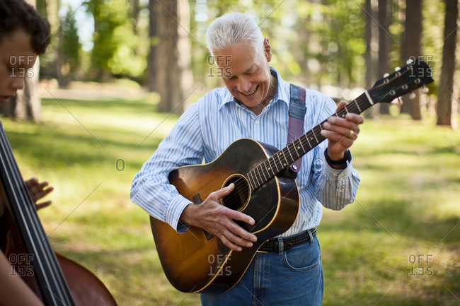 Smiling senior man playing an acoustic guitar while his grandson plays a double bass in a forest.