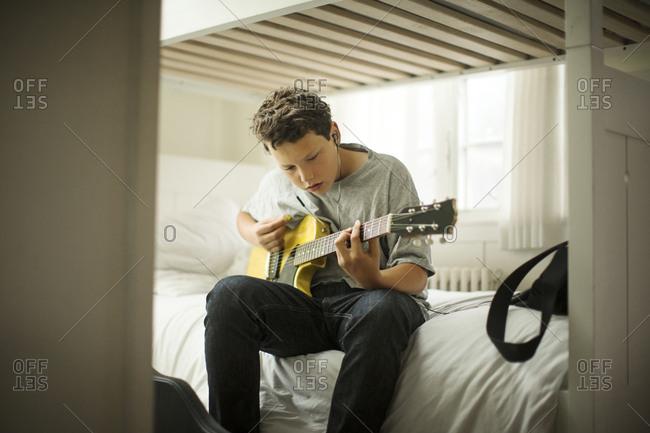 Teenage boy playing electric guitar.
