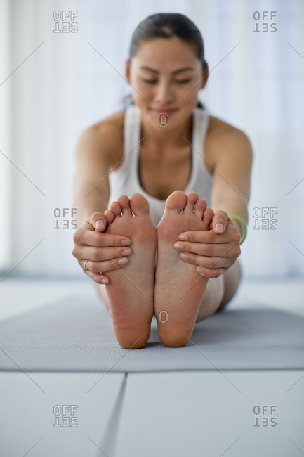 Happy young woman stretching her legs while practicing yoga.