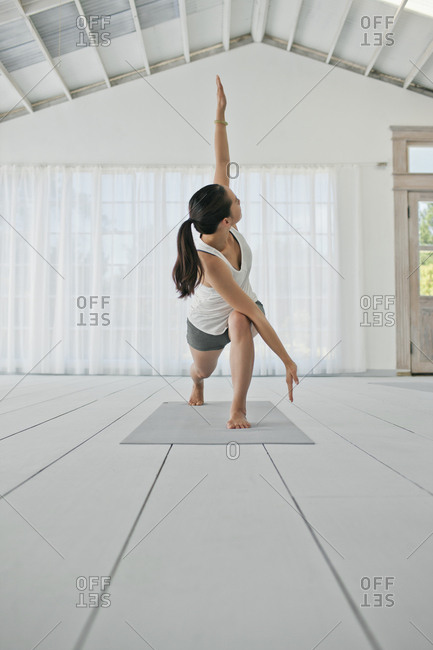 Happy young woman stretching her arms and legs while practicing yoga.