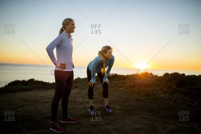 Two smiling young women take a break from their sunrise jog along the cliffs to admire the view of the ocean.