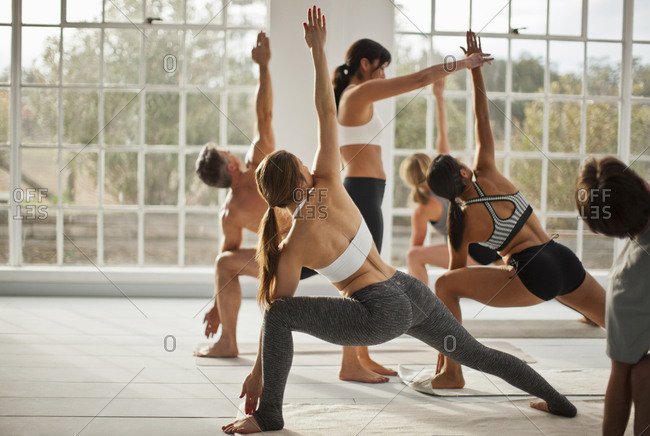 People practicing the warrior pose during a yoga class.