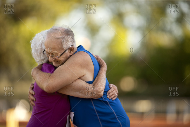 Loving senior couple embracing after an athletics event.