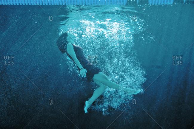 Woman wearing a dress swimming underwater.