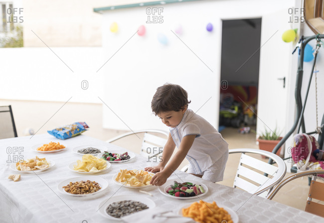 Little boy eating snacks before his birthday party
