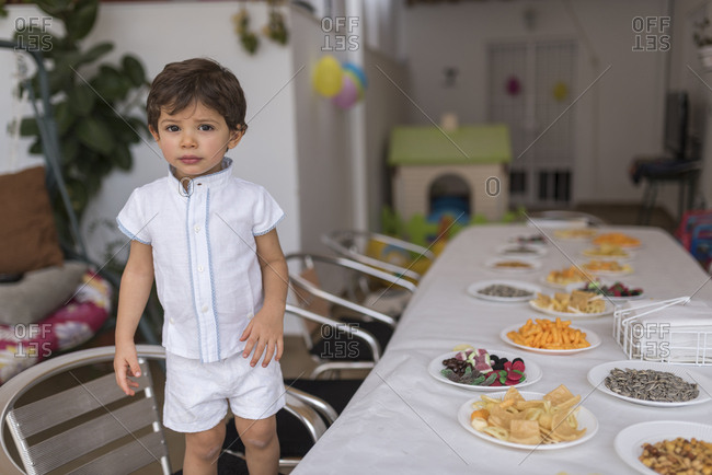 Little boy next to table with snacks before his birthday party