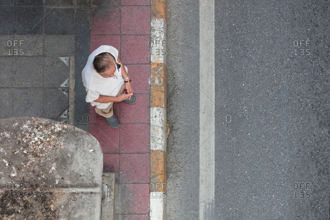 Bangkok, Thailand - 11 February, 2018: Overhead view of elderly man waiting by side of road