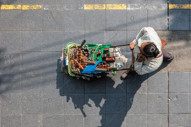Bangkok, Thailand - 11 February, 2018: Overhead view of man pushing cart full of tools talking on phone