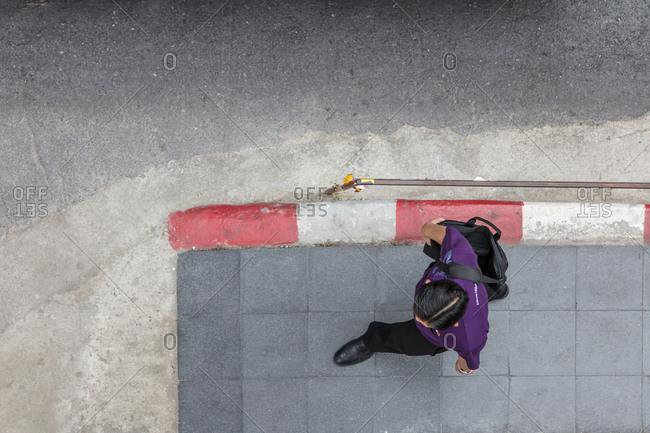 Bangkok, Thailand - 11 February, 2018: Overhead view of man walking to work