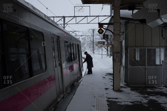 Japan - January 10, 2018: Senior man with cane boarding a train