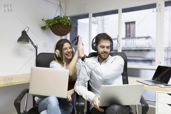 Young woman and male co-worker working on laptops high five each other