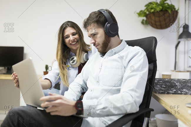 Young woman showing male co-worker something on screen of laptop