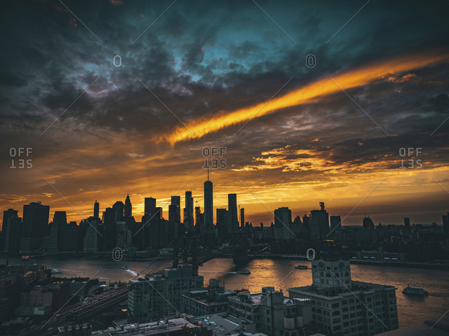 USA, New York, New York City - August 6, 2017: High angle view of silhouette cityscape against cloudy sky during sunset