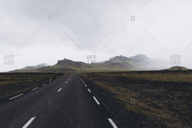 Empty road leading towards mountain against cloudy sky