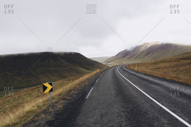 Empty road amidst mountains against cloudy sky