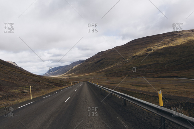 Empty road amidst mountains against cloudscape