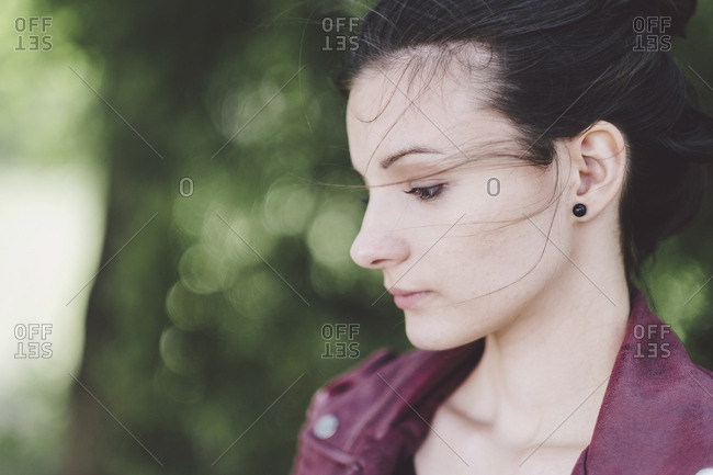 Close-up of thoughtful woman looking away while standing at park