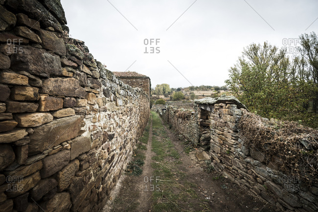 Footpath amidst old stone wall against sky