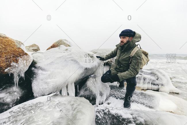 Man crouching by frozen rocks at beach