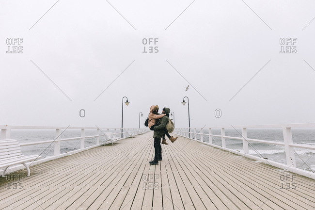 Boyfriend carrying girlfriend while standing on pier against clear sky
