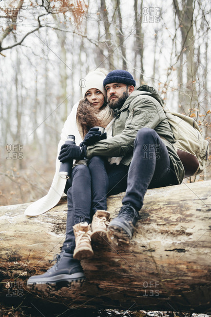 Couple sitting on fallen tree at forest