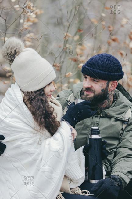 Loving girlfriend feeding drink to boyfriend at forest