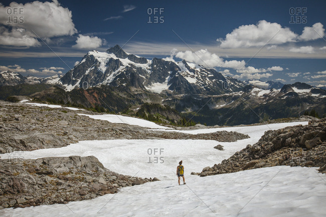 Mid distance view of female hiker standing on snow against mountains and cloudy sky during winter at North Cascades National Park