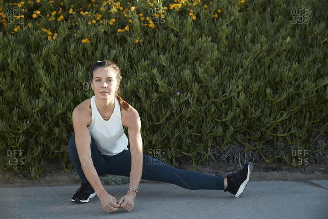 Portrait of confident woman stretching legs against plants on footpath