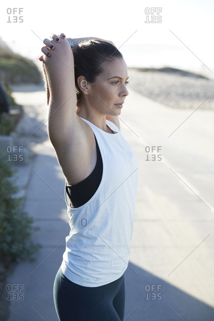 Determined woman stretching arms on footpath