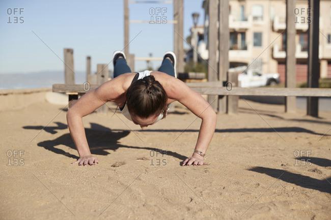 Woman doing push-ups at beach