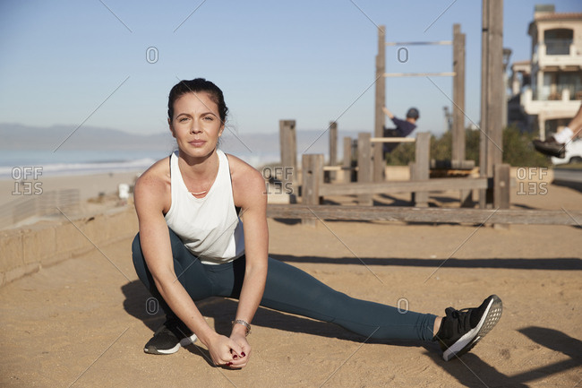 Portrait of confident woman stretching legs at beach