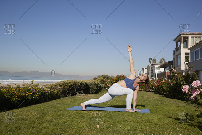 Full length of woman with legs apart and arms outstretched practicing yoga on exercise mat