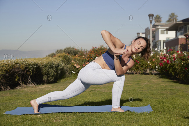 Full length of woman with legs apart and hands clasped practicing yoga on exercise mat