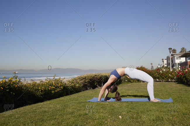 Full length of woman bending over backwards on exercise mat against clear sky