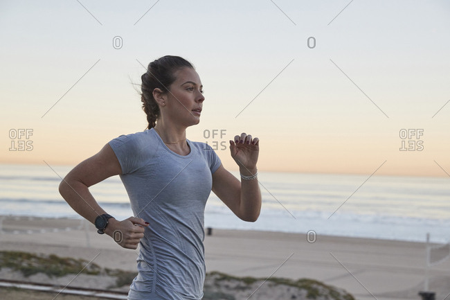 Side view of woman jogging against sea and clear sky