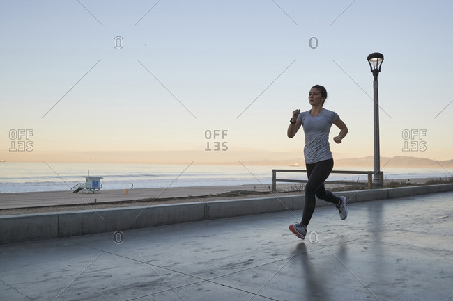 Full length of woman jogging against sea and clear sky
